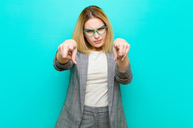 Jovem mulher bonita loira apontando para a frente com os dedos e expressão de raiva, dizendo para fazer o seu dever contra plana