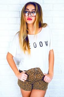Jovem mulher bonita loira com lábios brilhantes e sensuais, usando óculos e short com estampa animal