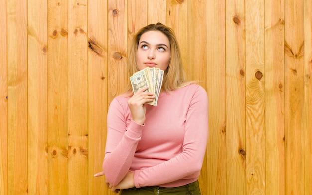 Jovem mulher bonita loira com notas de dólar contra a parede de madeira