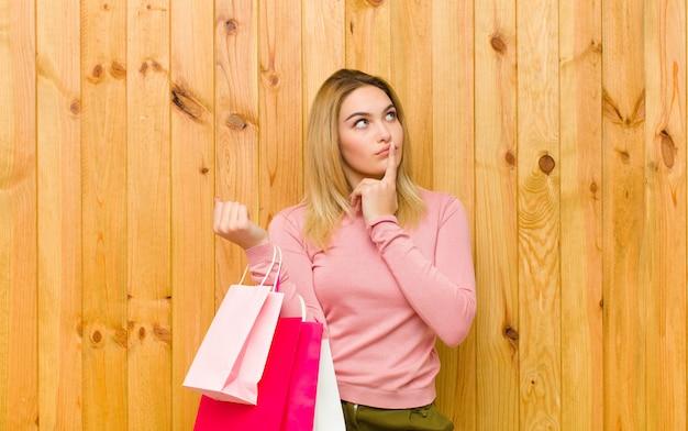 Jovem mulher bonita loira com sacos de compras contra madeira