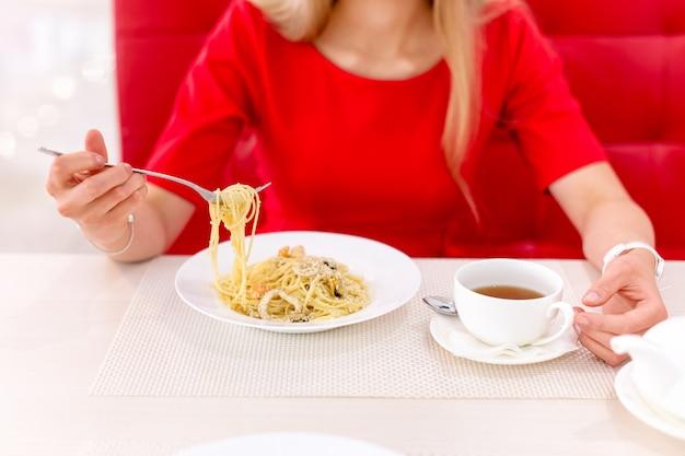 Jovem mulher bonita loira comendo no restaurante