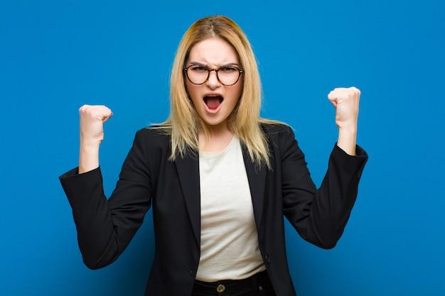Jovem mulher bonita loira gritando agressivamente com uma expressão de raiva ou com os punhos cerrados, comemorando o sucesso contra a parede plana