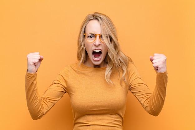 Jovem mulher bonita loira gritando agressivamente com uma expressão de raiva ou com os punhos cerrados comemorando sucesso contra a parede de cor lisa