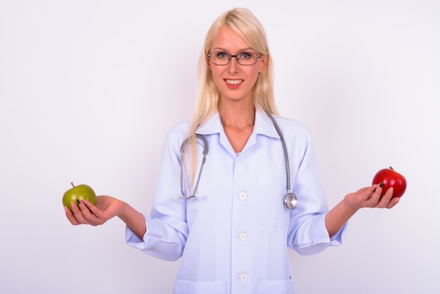 Jovem mulher bonita loira médica com óculos contra o espaço em branco