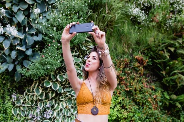 Jovem mulher bonita loira na rua tirando uma foto com o celular e sorrindo. verão, fundo verde