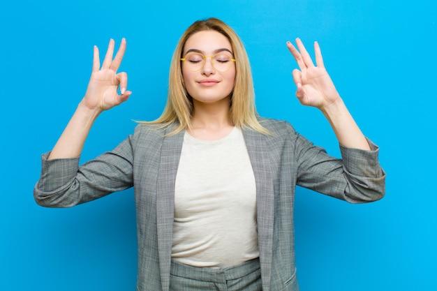 Jovem mulher bonita loira olhando concentrado e meditando, sentindo-se satisfeito e relaxado, pensando ou fazendo uma escolha na parede plana