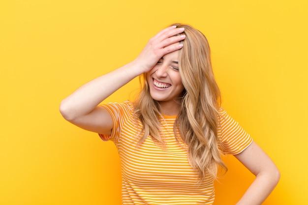 Jovem mulher bonita loira rindo e batendo na testa como dizer dããããããão! eu esqueci ou isso foi um erro estúpido contra parede de cor lisa