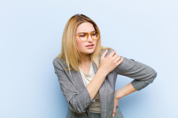 Jovem mulher bonita loira se sentindo cansado, estressado, ansioso, frustrado e deprimido, sofrendo com dor nas costas ou pescoço contra parede plana