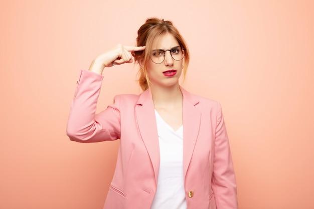 Jovem mulher bonita loira se sentindo confuso e confuso, mostrando que você é louco, louco ou louco. conceito de negócios
