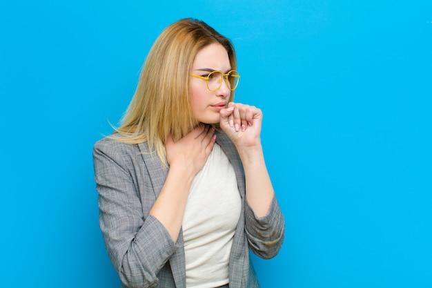 Jovem mulher bonita loira se sentindo doente com uma dor de garganta e sintomas de gripe, tosse com a boca coberta contra plana