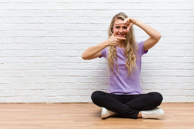 Jovem mulher bonita loira se sentindo feliz, amigável e positivo, sorrindo e fazendo um retrato ou moldura com as mãos