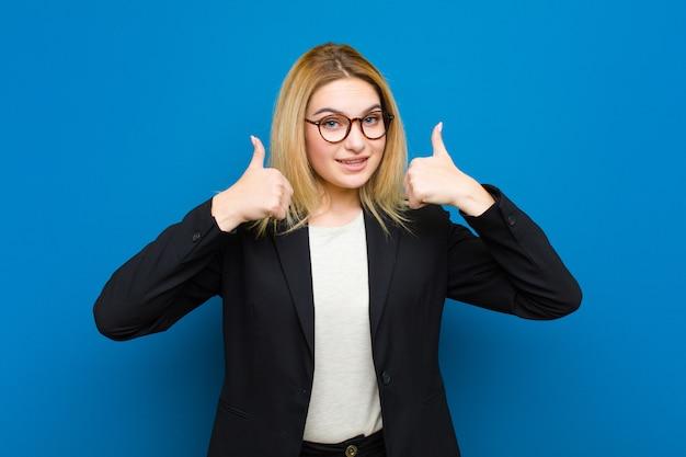 Jovem mulher bonita loira sorrindo amplamente olhando feliz, positivo, confiante e bem sucedido, com os dois polegares para cima