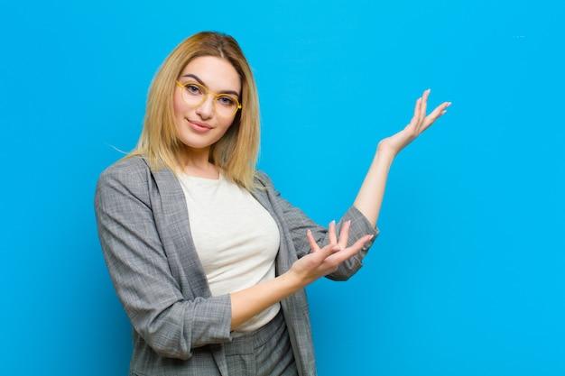 Jovem mulher bonita loira sorrindo com orgulho e confiança, sentindo-se feliz e satisfeito e mostrando um conceito no espaço da cópia contra a parede plana