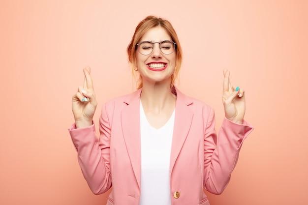 Jovem mulher bonita loira sorrindo e cruzando ansiosamente os dois dedos, sentindo-se preocupado e desejando ou esperando boa sorte
