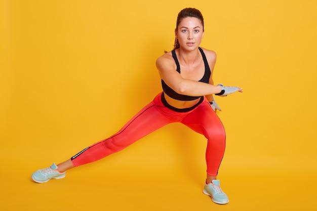 Jovem mulher bonita malhando, fazendo lunges laterais, viscosos exercícios para pernas, quadris e nádegas, fêmea desportiva usa top preto e leggins, isolados na parede amarela.