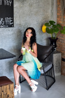 Jovem mulher bonita morena com vestido elegante de verão, debruçada sobre um café, bebendo um coquetel saboroso e esperando por seus amigos.