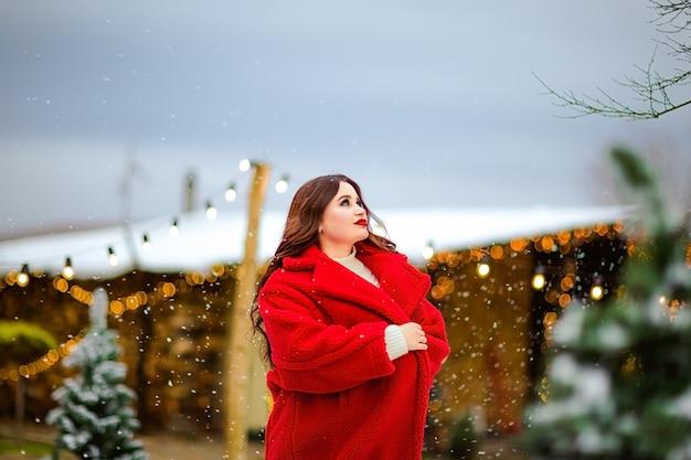 Jovem mulher bonita morena de casaco longo vermelho patinando na pista de patinação aberta. fundo de natal.