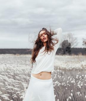 Jovem mulher bonita morena de pé no campo com trigo