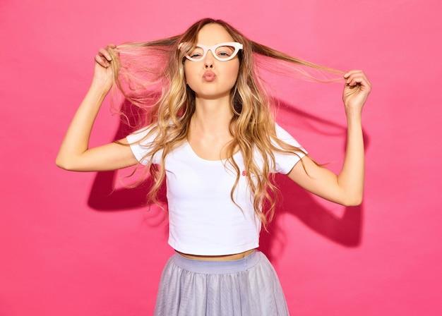 Jovem mulher bonita. mulher na moda em roupas de verão casual em óculos de sol adereços falsos. linguagem corporal de expressão facial de emoção feminina positiva. modelo engraçado, brincando com o cabelo na pi