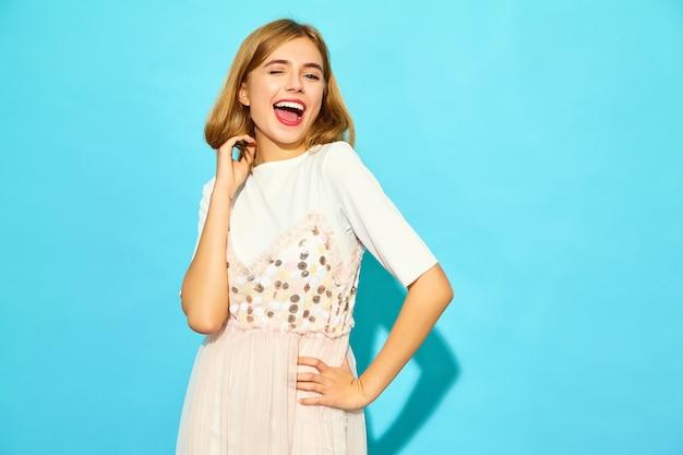 Jovem mulher bonita. mulher na moda em roupas de verão casual está piscando. modelo engraçado isolado na parede azul
