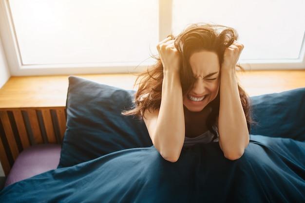 Jovem mulher bonita na cama de manhã em casa. mantenha as mãos na cabeça perto das orelhas e sofra de dor e dor de cabeça. ruas e manhã dolorosa.