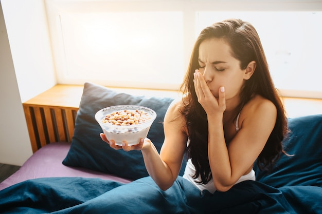 Jovem mulher bonita na cama de manhã em casa. pessoa do sexo feminino se sentir doente depois de comer cereais com café da manhã