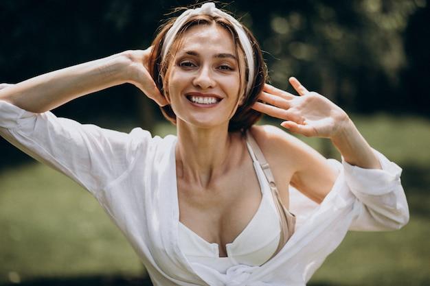 Jovem mulher bonita na camisa branca no quintal