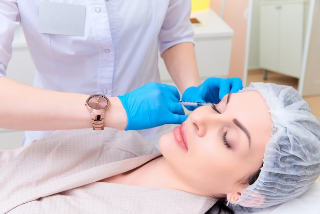 Jovem mulher bonita na clínica estética da cosmetologia.