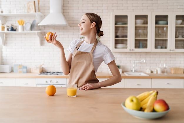 Jovem mulher bonita na cozinha com um avental, frutas e suco de laranja