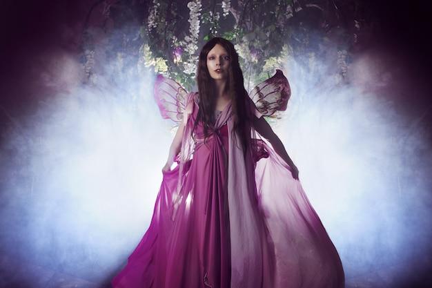 Jovem mulher bonita na imagem de fadas, magia floresta escura