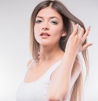 Jovem mulher bonita na parte superior da camiseta de alças que guarda a mão no cabelo.