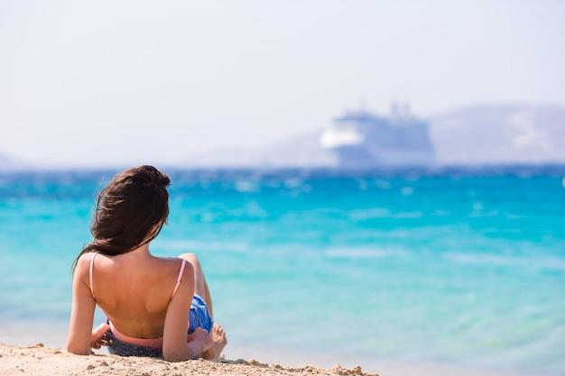 Jovem mulher bonita na praia durante férias tropicais. a menina aprecia seu wekeend em uma das praias bonitas em mykonos, grécia, europa.