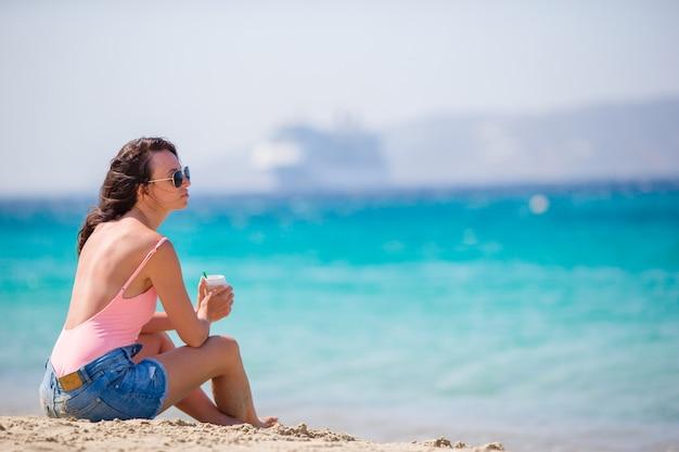 Jovem mulher bonita na praia na europa. menina com café de férias em mykonos, grécia