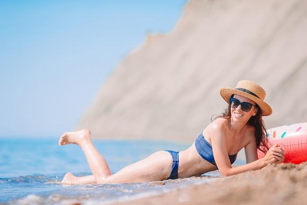 Jovem mulher bonita na praia tomando banho de sol