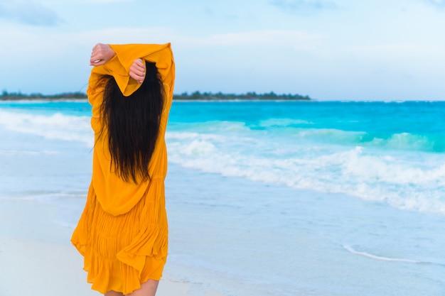 Jovem mulher bonita na praia tropical no pôr do sol.
