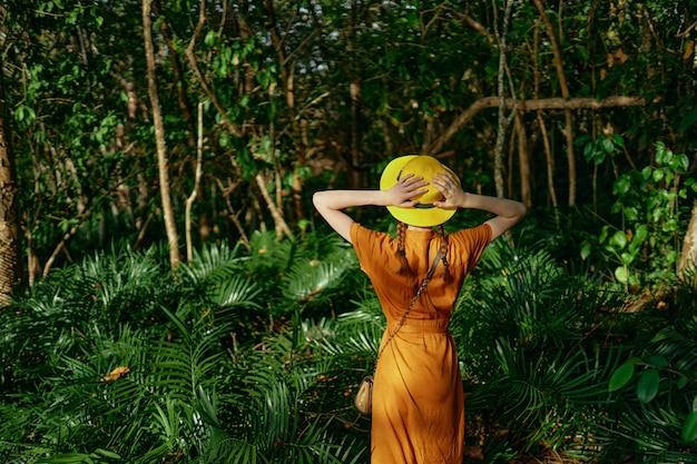 Jovem mulher bonita na selva tropical com chapéu passeios no parque, naturalista