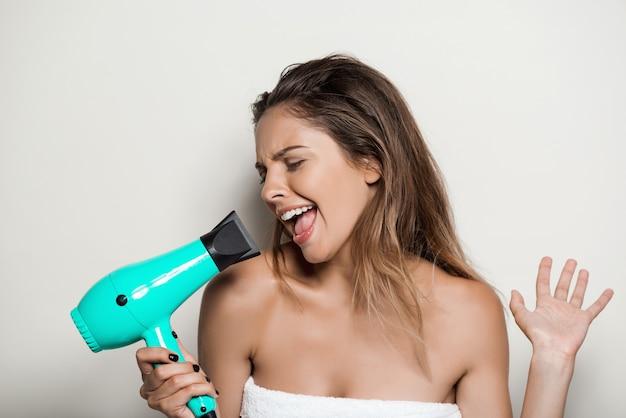 Jovem mulher bonita na toalha cantando com secador de cabelo