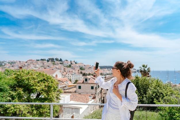 Jovem mulher bonita na varanda com vista para uma pequena cidade na croácia