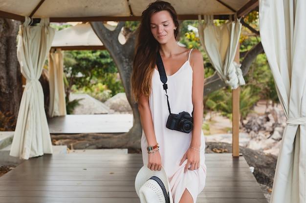 Jovem mulher bonita natural em vestido claro, posando em uma tenda, férias tropicais,