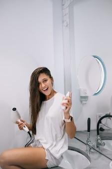 Jovem mulher bonita no banheiro segurando um secador de cabelo e uma pequena garrafa, vista de perto