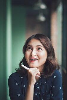 Jovem mulher bonita no café perto da janela, pensando e escrevendo algo.