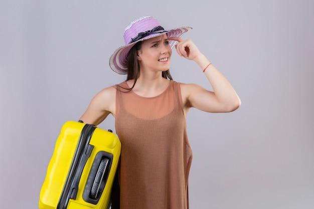 Jovem mulher bonita no chapéu do verão segurando a mala amarela, olhando de lado apontando o templo pensando com expressão pensativa, tendo dúvidas sobre a parede branca