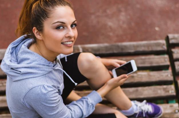 Jovem mulher bonita no equipamento desportivo que guarda um smartphone nas mãos ao sentar-se em um banco de parque.