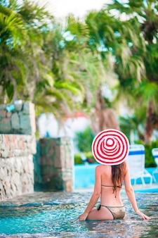 Jovem mulher bonita no grande chapéu vermelho, aproveitando as férias de verão na piscina tranquila