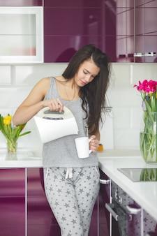 Jovem mulher bonita no início da manhã tomando café na cozinha. manhã fresca. bebida estimulante. taxas de trabalho. senhora acordada.