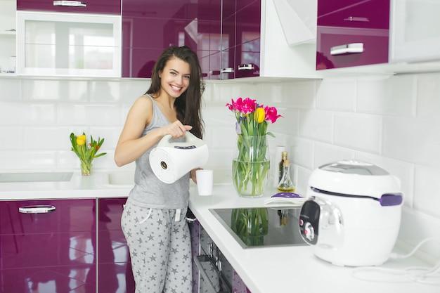 Jovem mulher bonita no início da manhã tomando café na cozinha. manhã fresca. bebida refrescante. senhora acordada.