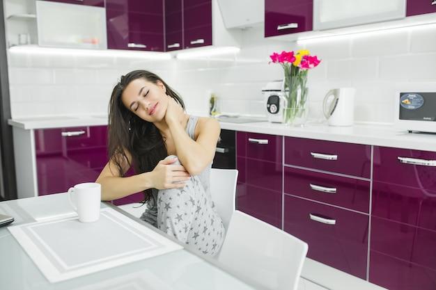 Jovem mulher bonita no início da manhã tomando café na cozinha. manhã fresca. bebida refrescante. taxas pelo trabalho. senhora acordada.