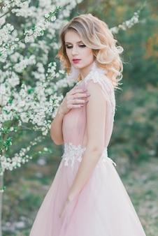 Jovem mulher bonita no jardim florescendo. noiva em vestido de noiva