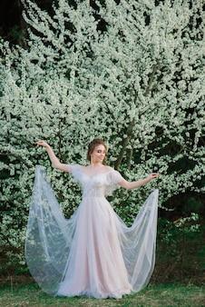 Jovem mulher bonita no jardim florescendo. noiva.