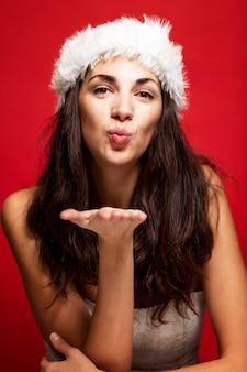 Jovem mulher bonita no sorriso do chapéu de papai noel. conto de natal. cartão postal. vertical. vermelho.